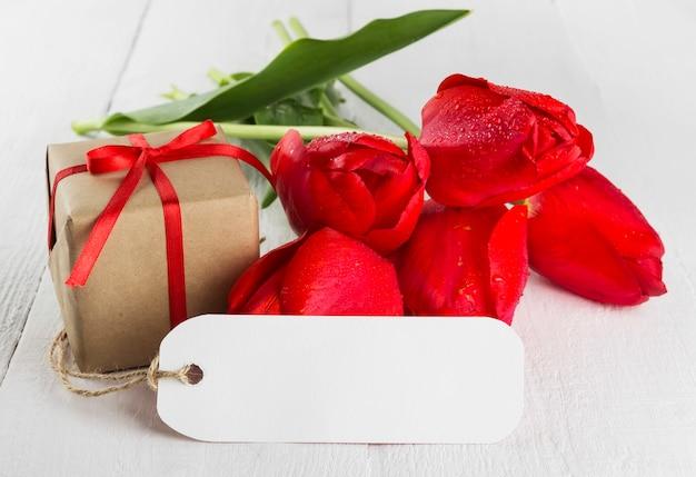 Tulipas vermelhas e presente em um fundo branco de madeira