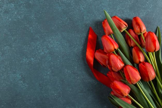 Tulipas vermelhas em azul, cartão postal em branco, férias de primavera, dia das mães. copie o espaço.