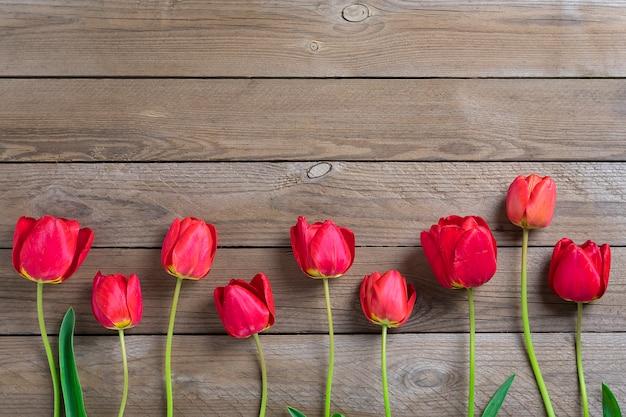 Tulipas vermelhas em fundo de madeira com espaço para texto, mensagem. dia das mães, olá primavera conceito.