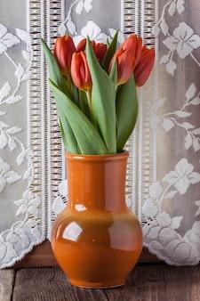 Tulipas vermelhas em pote de cerâmica