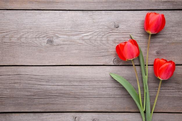 Tulipas vermelhas em um cinza de madeira.