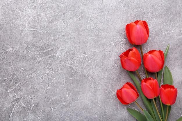 Tulipas vermelhas em um concreto cinzento.