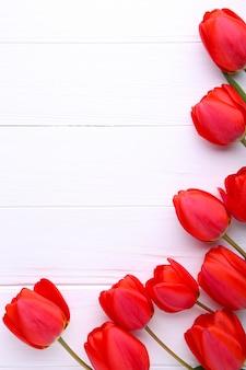 Tulipas vermelhas em um fundo branco de madeira
