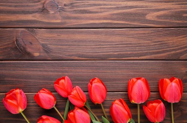 Tulipas vermelhas em um fundo de madeira marrom