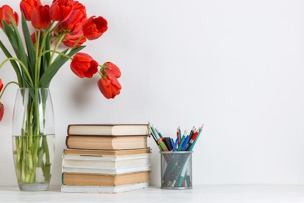 Tulipas vermelhas em um vaso, livros e material escolar em branco.