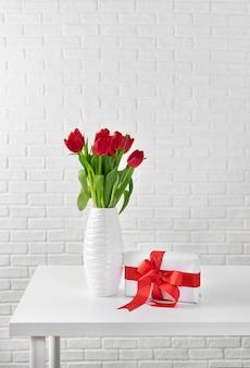 Tulipas vermelhas em vaso branco ao lado de uma caixa de presente com fita vermelha