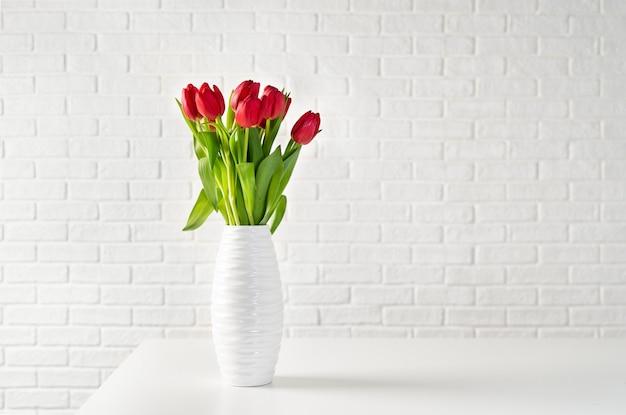 Tulipas vermelhas em vaso branco contra o fundo branco tijolos