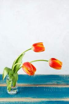 Tulipas vermelhas em vaso de vidro na mesa de madeira