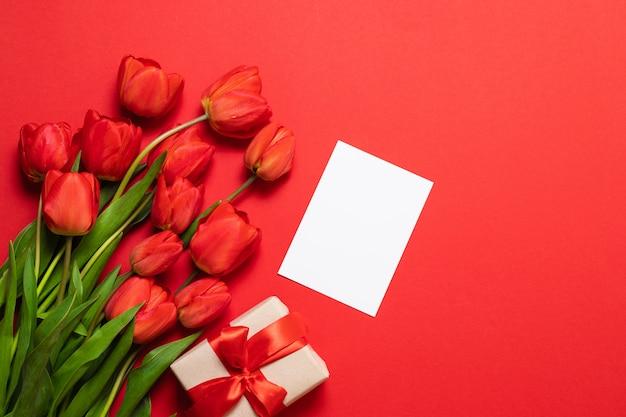Tulipas vermelhas frescas com caixa de presente e cartão branco
