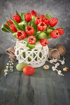 Tulipas vermelhas na superfície rústica com decorações de primavera,