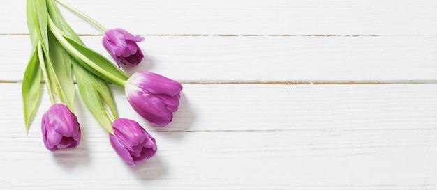 Tulipas violetas na mesa de madeira branca