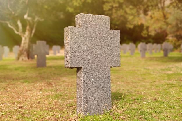 Tumba ensolarada com cruz de pedra