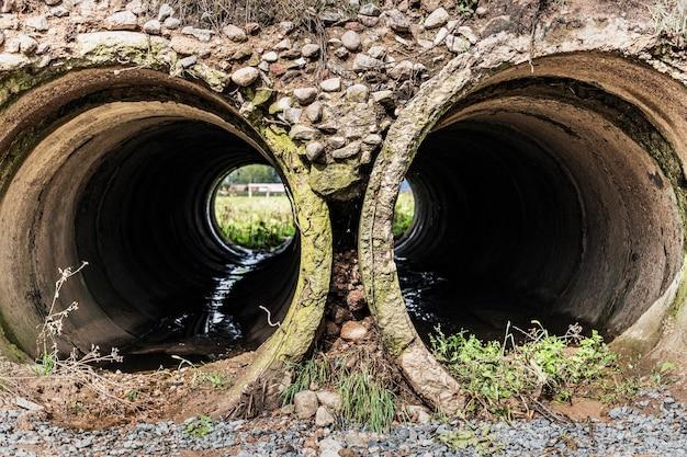 Túnel construído com tubos de concreto armado para drenagem das águas pluviais sob a estrada. vista através de um grande cano.