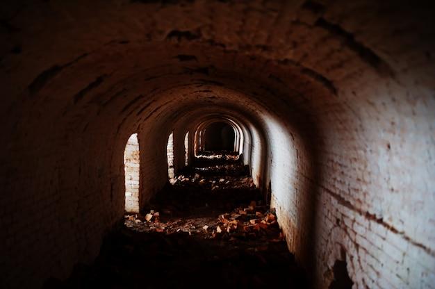 Túnel de arco de tijolo assustador no escuro e alguma luz.