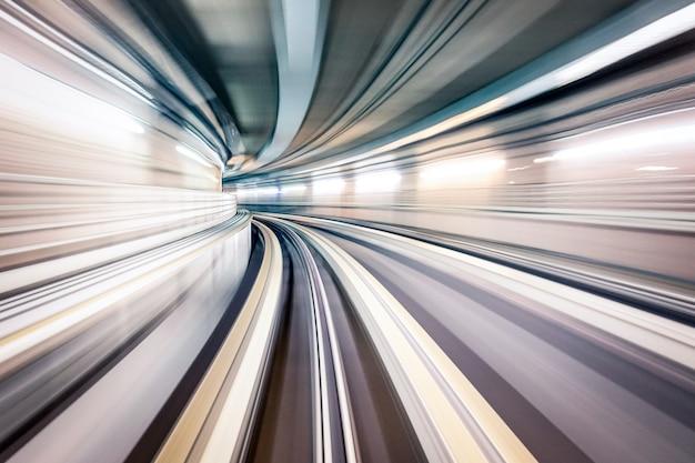 Túnel subterrâneo com trilhos borrados na galeria do metrô