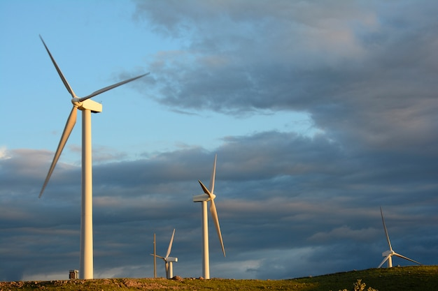 Turbina de turbinas de energia eólica na luz dourada na frente do céu nublado escuro