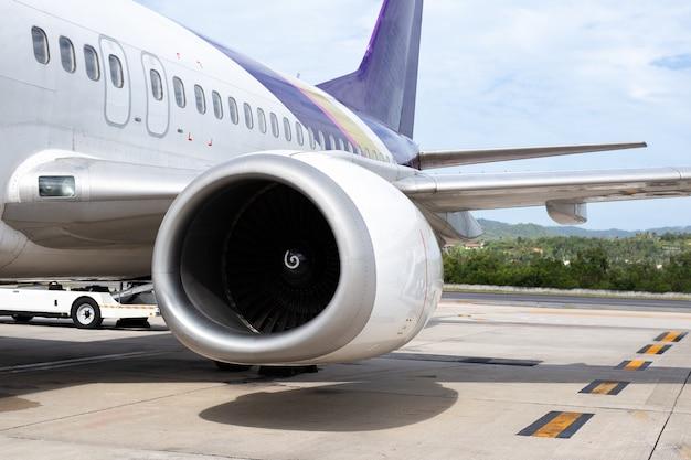 Turbina do avião do motor 737-400 no fundo tropical do aeroporto.