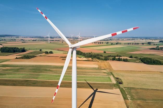 Turbina do moinho de vento no campo em dia de verão, gerador eólico rotativo