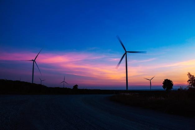Turbina eólica de silhueta com o céu azul à noite.