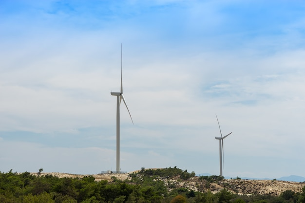 Turbina eólica na grama verde sobre o céu azul nublado