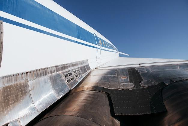 Turbinas abaixo da asa branca do velho avião ficam ao ar livre