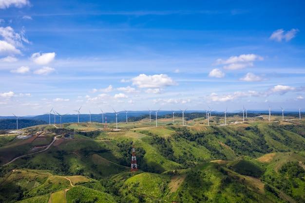 Turbinas de vento de paisagem na terra de montanha e fundo de céu azul
