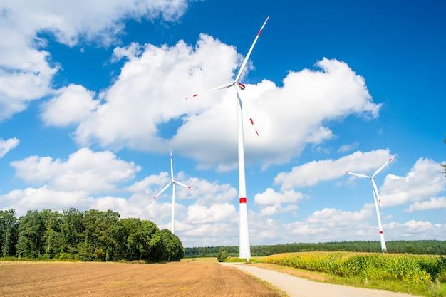 Turbinas em campo no céu azul nublado. parque eólico na baixa saxônia, alemanha. aquecimento global, mudança climática. fonte de energia alternativa. eco poder, conceito de tecnologia verde.