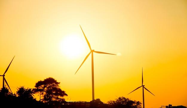 Turbinas eólicas de silhueta no campo de terra com o céu do sol