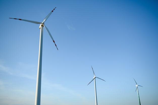 Turbinas eólicas em um campo verde e céu azul.