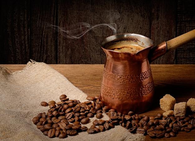 Turco de cobre com café acabado de fazer quente num fundo de madeira com grãos de café