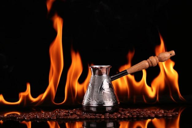 Turco em grãos de café em um fundo de fogo, fundo preto. conceito vivacidade e energia