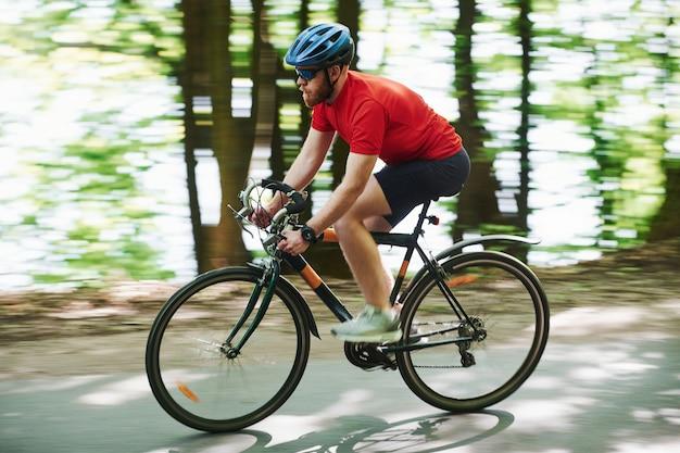 Turing para a esquerda. ciclista de bicicleta está na estrada de asfalto na floresta em um dia ensolarado