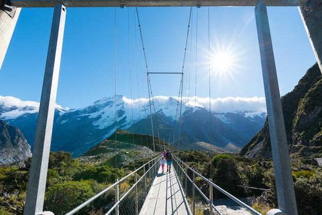 Turismo andando na ponte suspensa sobre o rio na nova zelândia