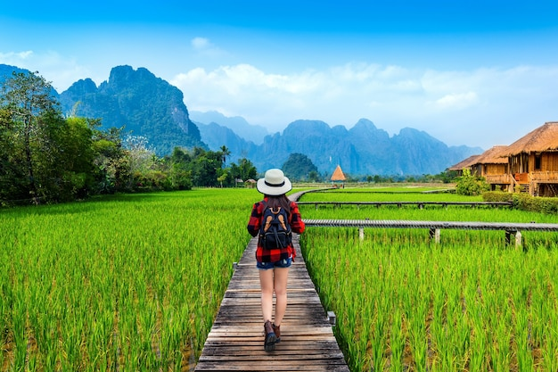 Turismo com mochila caminhando em caminho de madeira, vang vieng no laos.