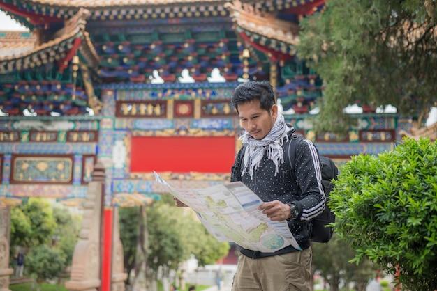 Turismo de homem bonito, viajante com câmera, mapas, mochila e tripé, fundo de arquitetura chinesa na província de yunnan, china