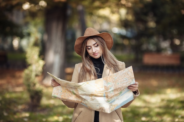 Turismo de outono. jovem viajante atraente é guiada pelo mapa da cidade.
