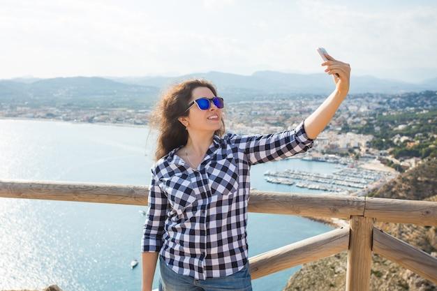 Turismo de viagens e conceito de férias jovem feliz tomando selfie perto do mar