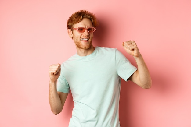 Turismo e conceito de férias. homem ruivo alegre se divertindo na festa, dançando e curtindo as férias, de pé em óculos escuros e camiseta contra o fundo rosa.