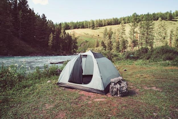 Turismo e conceito de viagens. paisagem linda de verão com montanhas e barraca do turista. tenda verde fica perto do lago nas montanhas.