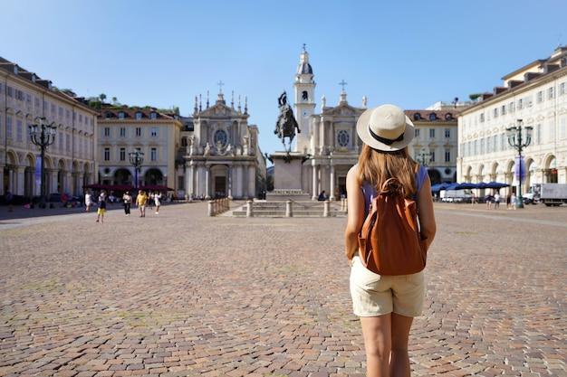 Turismo em torino, itália. vista traseira da garota viajante andando na praça san carlo, apreciando a vista da cidade de turim, itália. mochileiro feminino jovem visitando a europa.