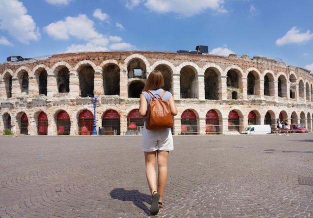 Turismo em verona. vista traseira da mulher turista caminha em direção à arena de verona, itália.