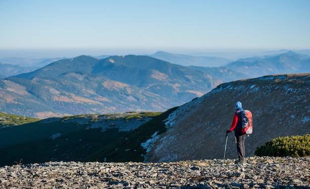 Turismo feminino em pé no cume da montanha, apreciando a vista aberta sobre as montanhas