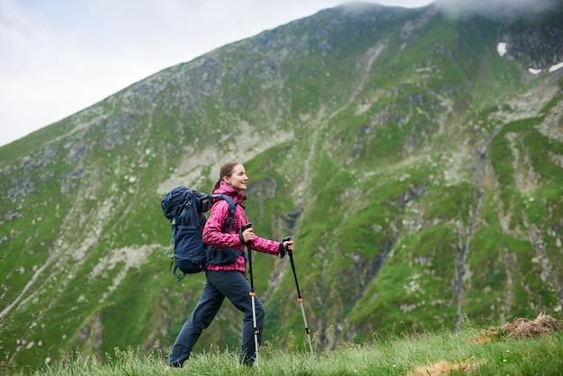 Turismo feminino subindo a encosta gramada verde com bengala e mochila na frente de belas montanhas rochosas