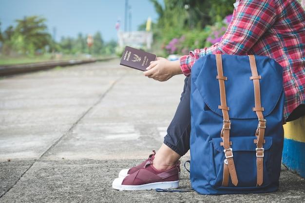 Turismo jovem mulher (passageiro) sentado e segurando o passaporte na plataforma da estação de trem