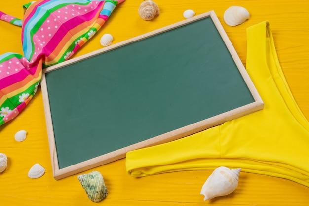 Turismo marítimo, uma placa de escrita verde colocada com vários objetos em um piso de madeira amarelo.