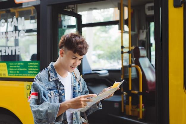 Turismo masculino asiático lendo um mapa na estação de ônibus.