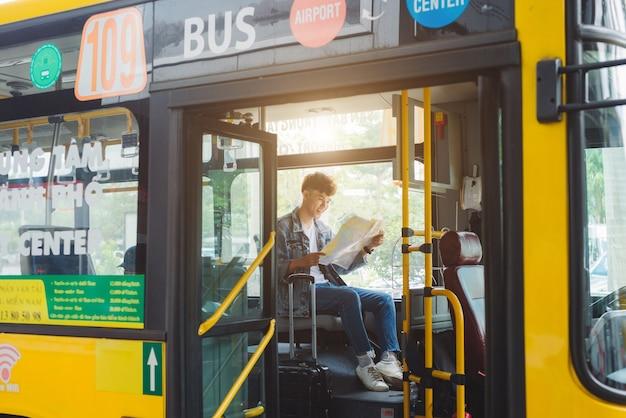 Turismo masculino asiático sentado no ônibus da cidade e lendo um mapa.