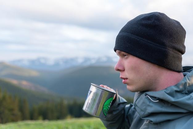Turismo masculino bebe café de uma caneca de metal