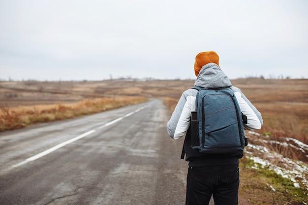 Turismo masculino caminha ao lado de uma estrada vazia de inverno na área suburbana com uma mochila. um homem viajante com chapéu laranja em uma rodovia.