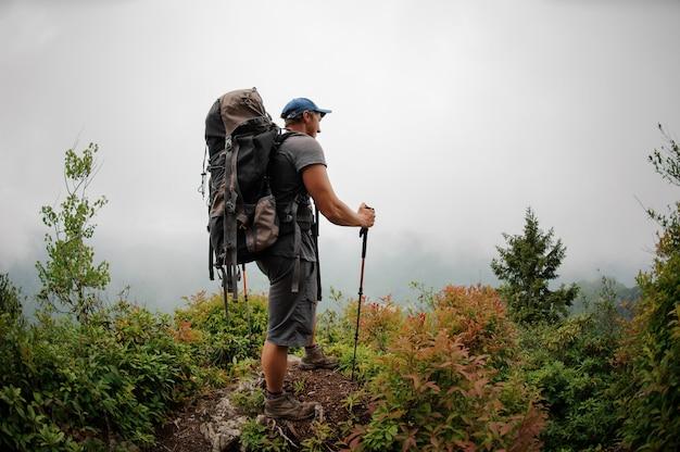 Turismo masculino com mochila em pé entre arbustos